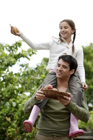 Girl sitting on man's shoulders with man holding a basket of pears photo