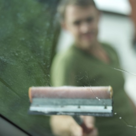 Man washing windshield with squeegee photo