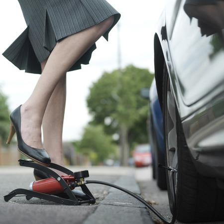 Businesswoman stepping on air pump photo