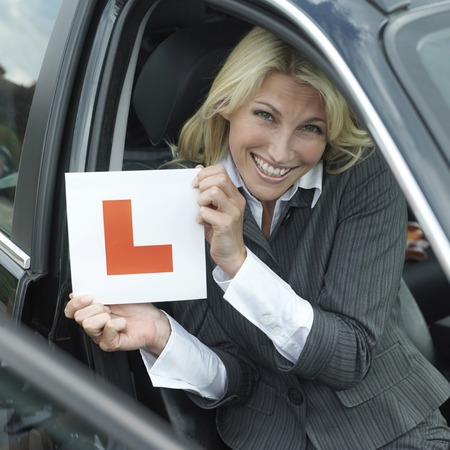 l plate: Businessman smiling while holding L plate Stock Photo
