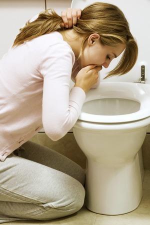 vomiting: Girl vomiting into toilet bowl Stock Photo