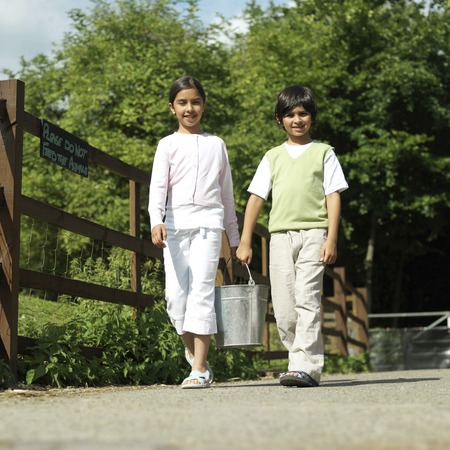 Boy and girl carrying a bucket together photo