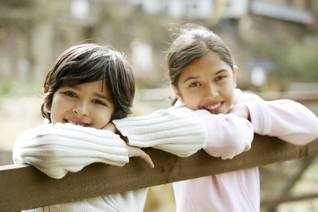he   my sister: Boy and girl leaning on wooden fence Stock Photo