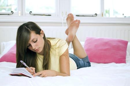 lying forward: Girl lying forward on the bed writing diary