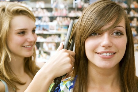 self conceit: Girl using hair iron on another girls hair
