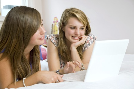 Girls lying forward on the bed using laptop photo