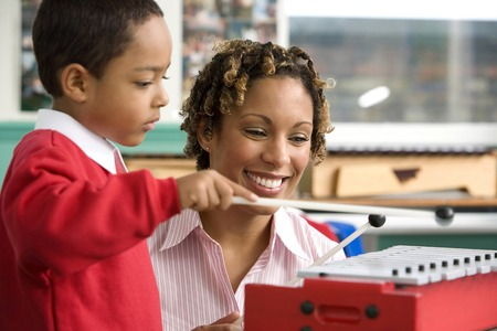 Woman teaching boy to play xylophone photo