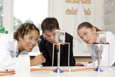 Woman with boy and girl carrying out science experiments Фото со стока
