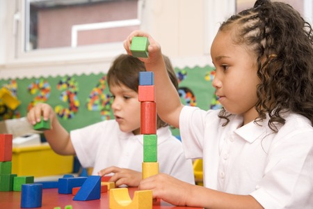 Boy and girl stacking up wooden blocks photo