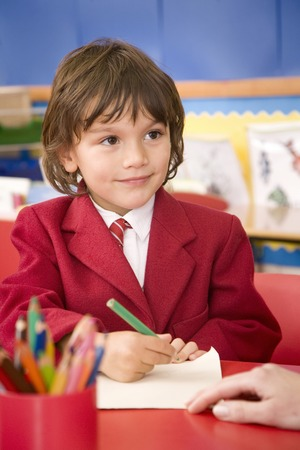 Boy smiling while holding coloured pencil