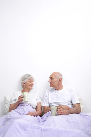 Senior man and woman drinking tea in the bedroom photo