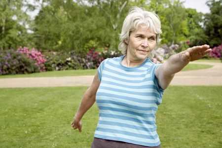 Senior woman practising yoga in the park