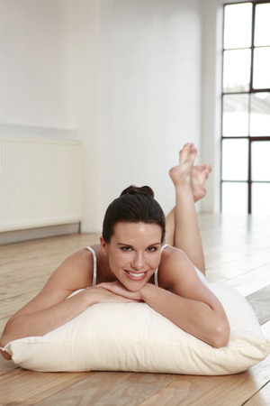 Woman lying on pillow with legs up
