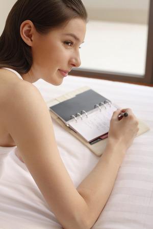 Woman lying forward in bed writing diary Stock Photo