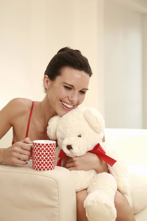 soft toy: Woman hugging a soft toy while holding a mug