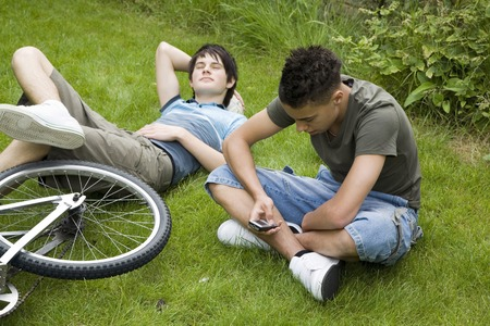 Boy text messaging on the phone, another boy resting on the grass photo