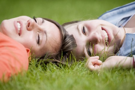 Girls lying on grass Stock Photo