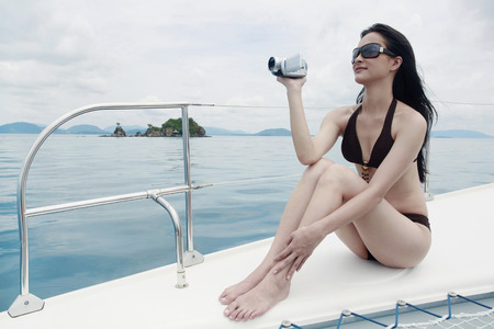 Woman in bikini using video camera on yacht photo