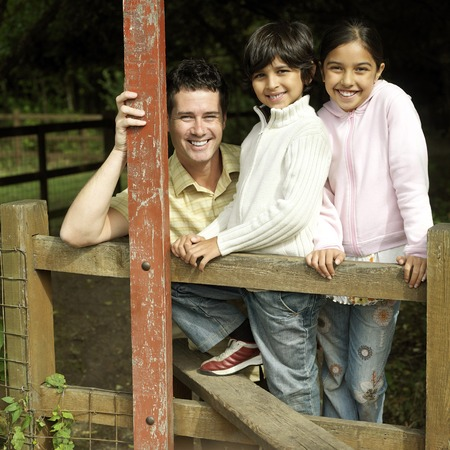 he   my sister: Man, boy and girl posing for the camera at the wooden fence Stock Photo