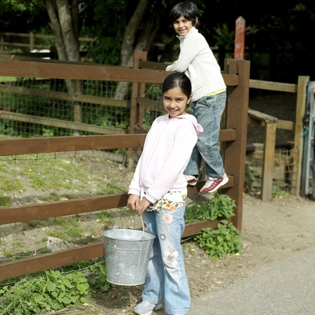 he   my sister: Girl with a bucket and boy standing on the fence, posing for the camera