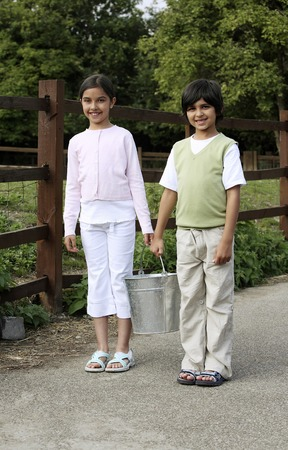 Boy and girl carrying a bucket