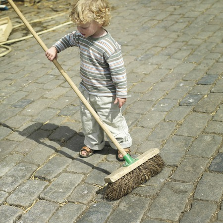 Boy holding a broom Stock Photo