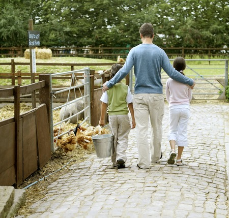 Man, girl and boy walking in a farm photo