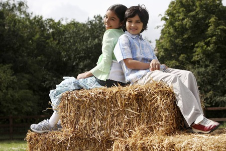 he   my sister: Boy and girl sitting on haystacks Stock Photo