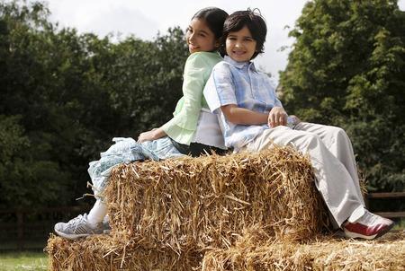 Boy and girl sitting on haystacks photo