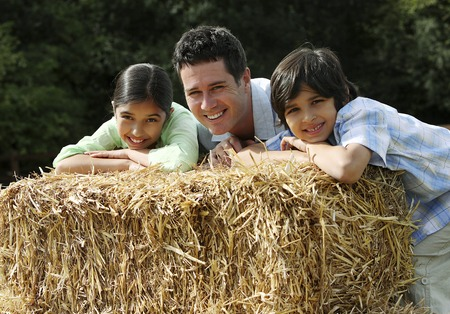 Man, boy and girl resting on haystack photo