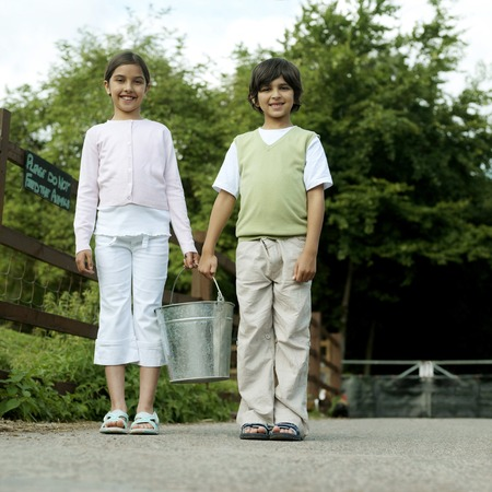 Boy and girl holding a bucket together photo