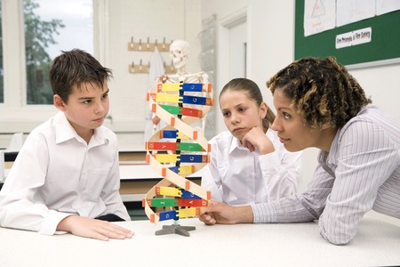 Woman teaching girl and boy using a molecular structure
