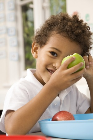 Boy covering one of his eyes with green apple