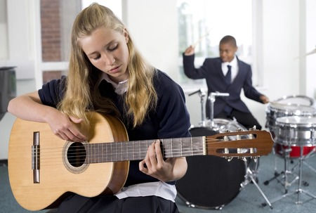 plucking: Girl plucking guitar with boy playing drum in the background