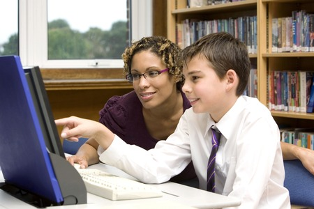 Woman assisting  boy using a computer photo