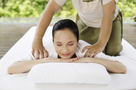 lays forward: Woman enjoying a body massage Stock Photo