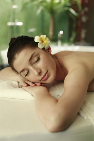 lays forward: Woman lying forward on the massage table with her eyes closed