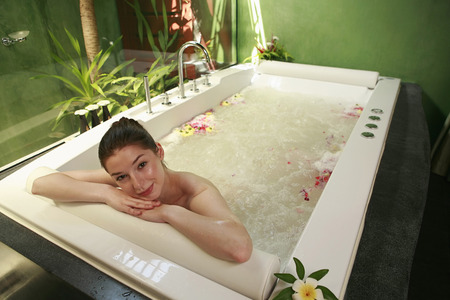 soaks: Woman in bathtub smiling at the camera