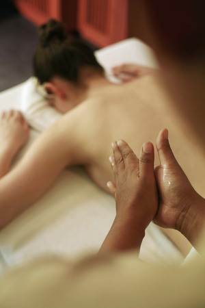 lays forward: Woman lying forward on massage table, massage therapist rubbing oil on her palms