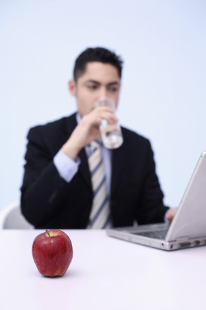 Businessman drinking water while using laptop photo