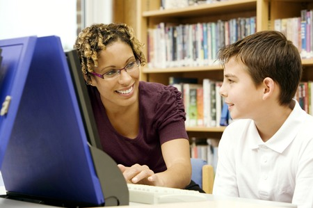 Woman assisting boy using a computer