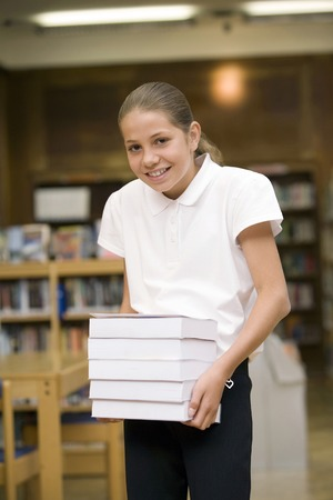 Girl carrying a stack of books photo