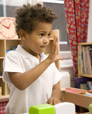 Boy gesturing while playing with toys photo