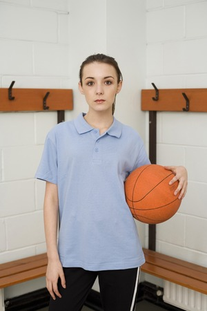 Girl holding basketball in the changing room