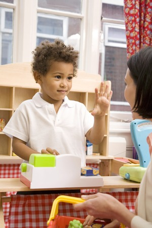 Boy gesturing while playing with toys, woman carrying basket Stock Photo