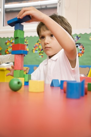 Boy stacking up wooden blocks Stock Photo