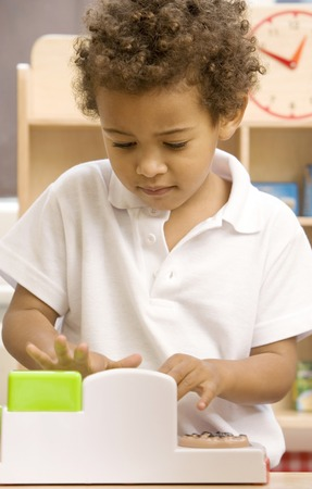 Boy playing with toy cash register photo