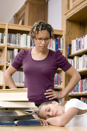 Woman looking at girl sleeping in the library photo