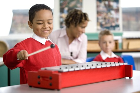 Woman talking to her student while another boy is playing the xylophone