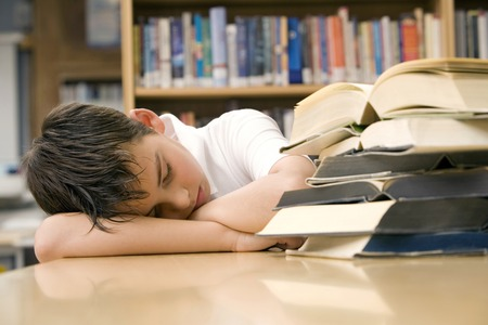 Boy sleeping beside a stack of books Stock Photo